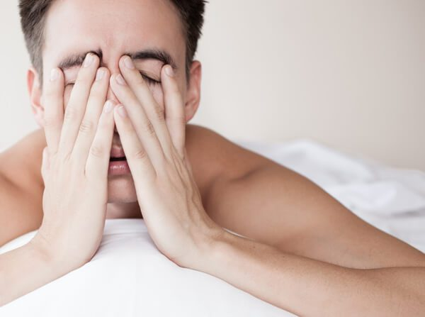 man holding tired face on bed
