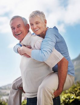 healthy elderly couple piggy backing