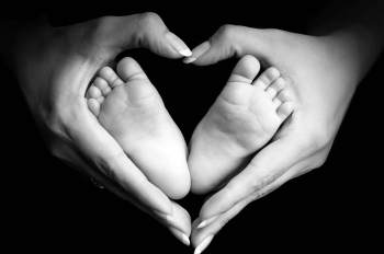 womans hands around baby's feet