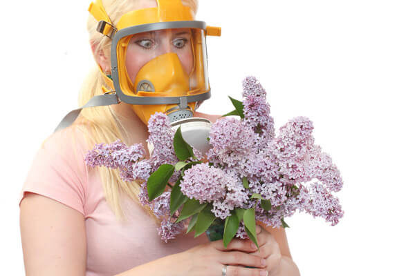 woman with gas mask around flowers
