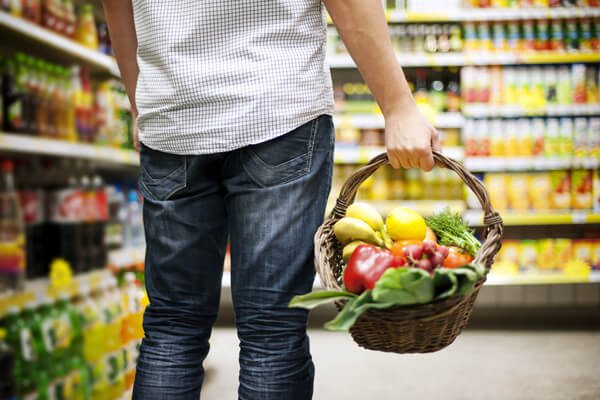 man holding shopping basket with healthy food