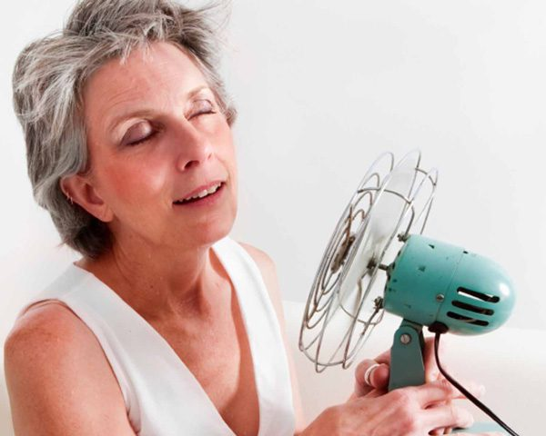middle aged woman holding fan to cool down